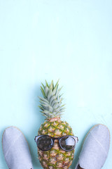 Pineapple, summer shoes and glasses from the sun. Blue background. Holidays. flat lay. copy space