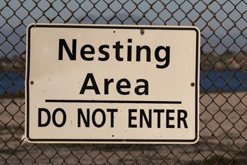 Nesting area do not enter sign on chain link fence