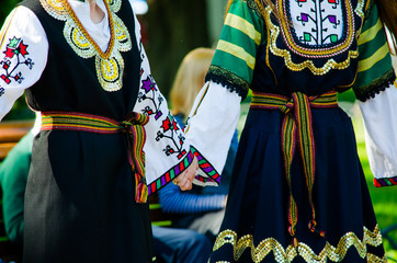 Girls in traditional green Bulgarian dresses holding hands