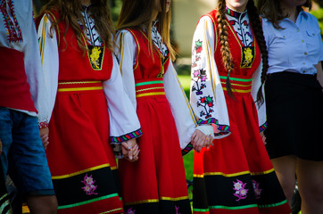 Unrecognizable girls in traditional Bulgarian costumes with red dresses and patterns on white shirts holding hands