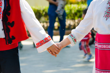 Bulgarian girl and a boy in ethnical red costumes holding hands