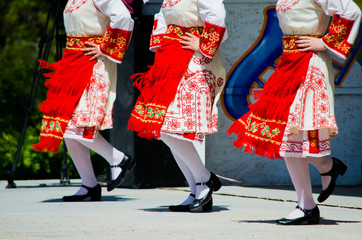 People in Bulgarian costumes with red colors dancing a traditional dance