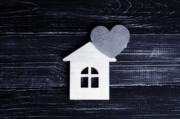 Wooden house with a red heart on a background of black wooden boards. A notification icon for the application. Love nest, love relationships. Buying a house with a young family. Affordable housing.