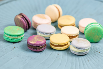 Close-up colorful French or Italian macaron on blue wooden table. Macarons is French dessert served...