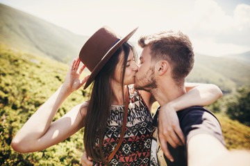 stylish hipster couple taking selfie and kissing on top of mountains in sunny summer day. beautiful man and happy woman in hat embracing on honeymoon. travel together
