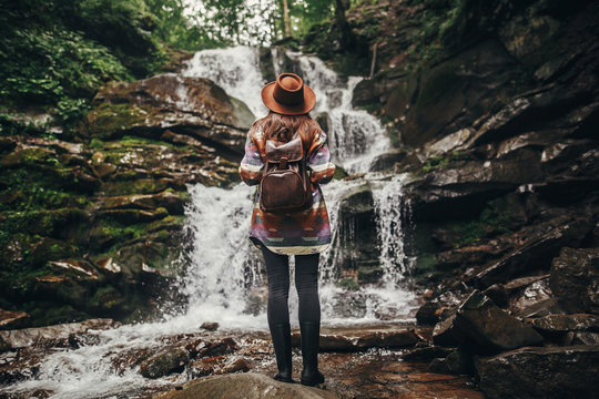 travel and wanderlust concept. stylish hipster girl in hat with backpack looking at waterfall in forest in mountains. traveler woman exploring woods.  summer vacation, space for text