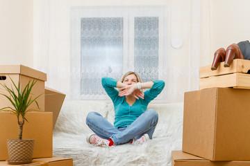 Photo of girl sitting on sofa among cardboard boxes