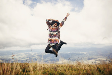 happy traveler hipster girl in hat, jumping with backpack and smiling in mountains in clouds. space for text. amazing atmospheric emotional moment. travel and wanderlust concept