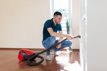 household, housework and cleaning concept - happy man with vacuum cleaner at home