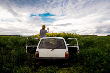 Rear view of woman photographing sunflowers on field while standing in car against cloudy sky