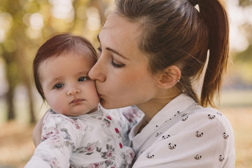Close-up of mother kissing cute daughter at park during autumn