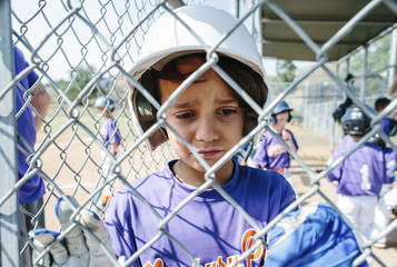 Close-up of sad boy standing in sports dugout seen through chainlink fence
