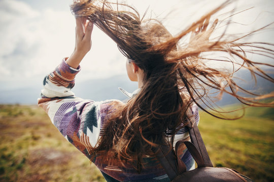 traveler hipster girl with windy hair and backpack, standing on top of sunny mountains. space for text. stylish woman waving hair. atmospheric moment. travel and wanderlust concept.