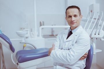 Your turn. Confident male dentist crossing hands while looking at camera