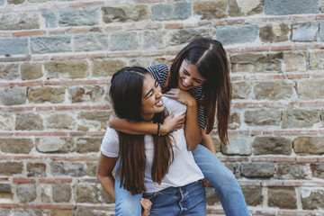 Happy woman piggybacking friend while standing by building