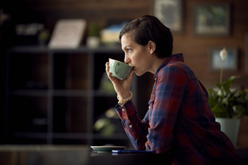 Side view of woman drinking coffee while standing in cafe