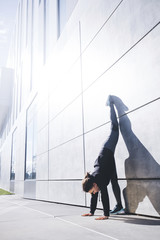 Woman doing handstand by wall