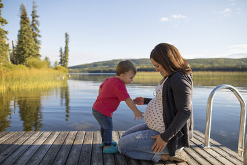 Side view of son touching pregnant mother's belly on pier over lake