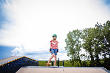 Portrait of girl skateboarding against cloudy sky at park