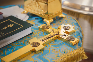 Christening in the church, golden religious utensils: bible, cross, prayer book, missal. Details in the orthodox christian church