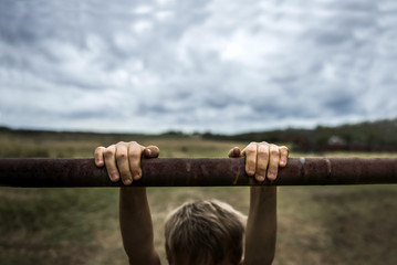 Cropped image of boy hanging on pole against cloudy sky
