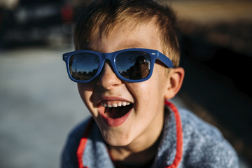 High angle close-up of happy boy wearing sunglasses while sitting outdoors