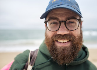 Close-up portrait of smiling bearded man wearing cap and eyeglasses at beach