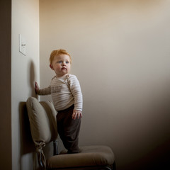 Cute baby boy looking away while standing on chair against wall at home