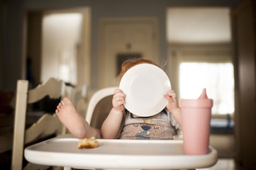 Baby boy holding plate while sitting on high chair at home