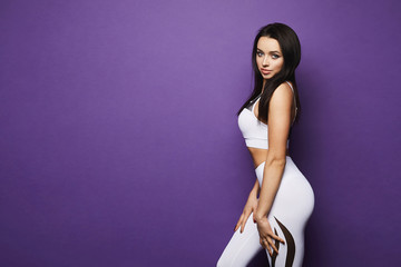 Sporty young sexy brunette woman with blue eyes and perfect body in sport outfit, tight white leggings and top with geometric patterns, isolated at violet background in studio