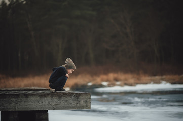 Side view of curious boy looking at river while crouching on wood at park