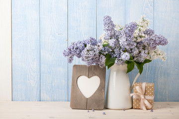 Lilac flowers in jug, gift box and heart shaped frame for greeting