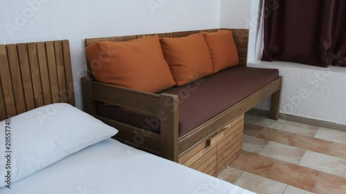 A Hotel Room With A White Double Bed Brown Sofa With Orange