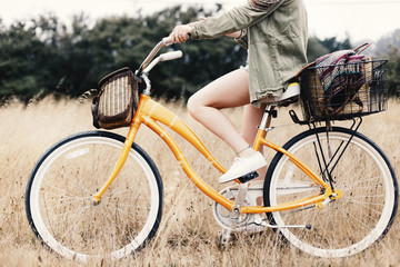 Low section of teenage girl riding bicycle amidst grassy field