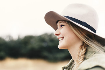 Side view of smiling teenage girl wearing hat while looking away on field