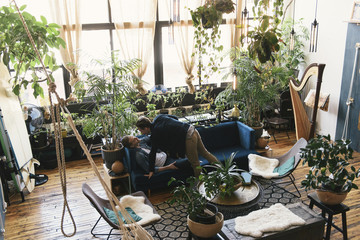 Loving gay couple amidst potted plants at home