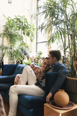 Loving Gay couple relaxing while sitting on sofa against potted plants at home