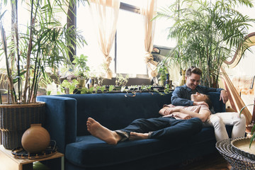 Loving Gay couple talking while relaxing on sofa against potted plants at home