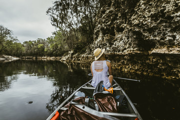 Rear view of young woman wearing hat while canoeing in lake at forest