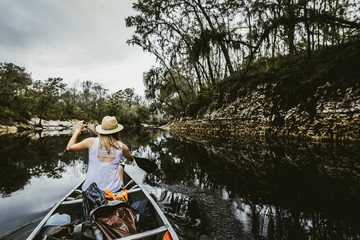 Rear view of young woman rowing canoe with oar in lake at forest