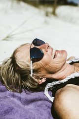 Cheerful mature woman wearing sunglasses while lying at beach during sunny day
