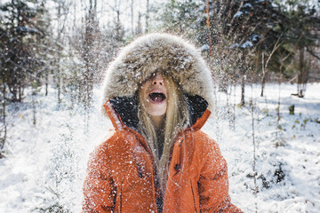 Woman in fur coat playing with snow in forest at Algonquin Park