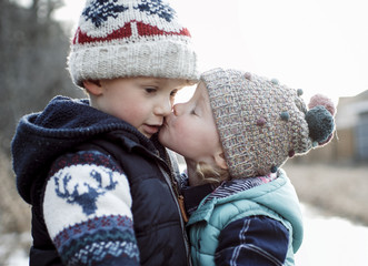 Loving sister kissing brother during winter