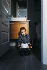 Portrait of boy defecating while sitting on potty seen through doorway at home