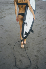 Low section of woman carrying surfboard while walking at beach