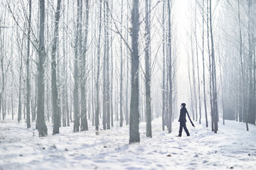 Full length of young man wearing black warm clothing while walking amidst trees at forest during foggy weather