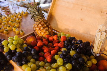 Assorted fresh fruits on plate. Apple, grapes, kiwi, pineapple, grapefruit, orange, banana and mint on wooden table. Selective focus