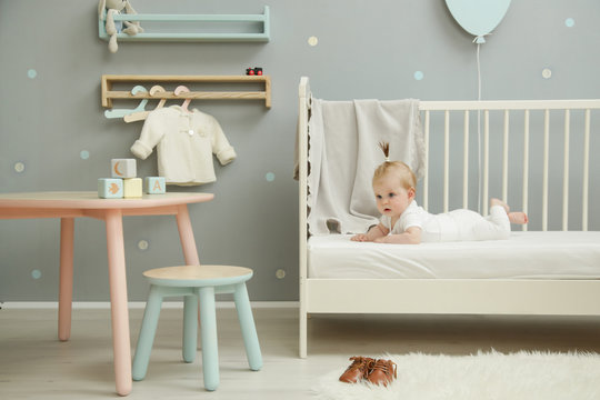 Adorable baby in the white outfit in the nursery