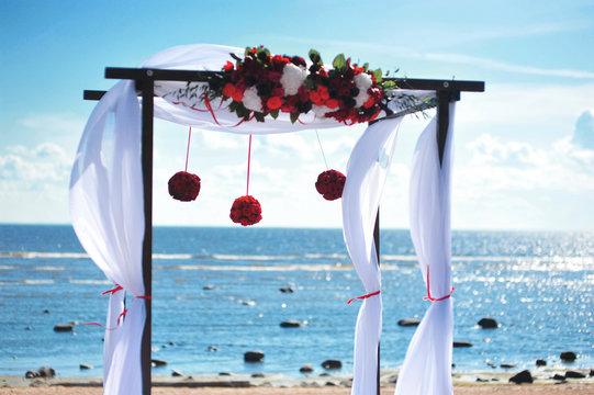 Blue beach wedding venue, wedding setup, cabana, arch, gazebo decorated with bright red flowers, beach wedding setup. Wedding decoration or event catering. Sunny summer day