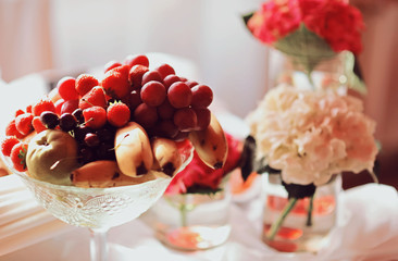 Catering wedding banquet table at reception. Restaurant presentation, food consumption, party concept. Fruit and flowers composition.